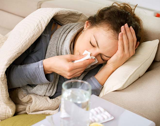 woman in bed with runny nose